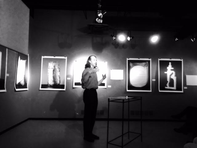 Black and white photo of Robert lecturing at a museum